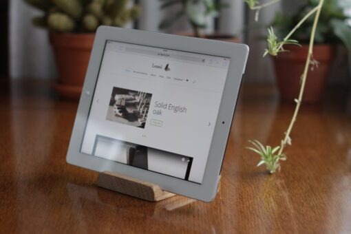 Oak adjustable tablet stand holding a tablet in landscape mode with plants in the background