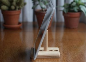 An oak tablet stand holding an iPad in portrait mode