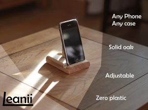 """Leanii oak phone stand holding a phone with words """"any phone, any case, solid oak, adjustable, zero plastic"""""""