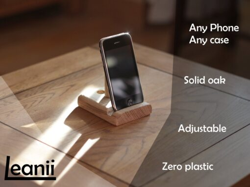 "Leanii oak phone stand holding a phone with words ""any phone, any case, solid oak, adjustable, zero plastic"""