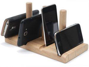 A solid chuck of oak holding several phones