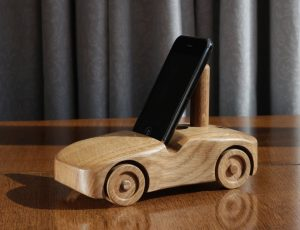 Oak wood phone stand in the shape of a car - 3rd angle with a small phone in portrait