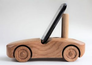 Oak wood phone stand in the shape of a car - side view with a small phone in portrait