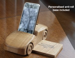 """Oak wood phone stand in the shape of a car - front and side view with base and text reading """"Personalised anti-roll base included"""""""