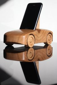 Oak wood phone stand in the shape of a car - front and side visible, reflected in table surface