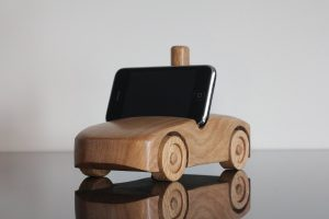 Oak wood phone stand in the shape of a car - front and side visible, black phone