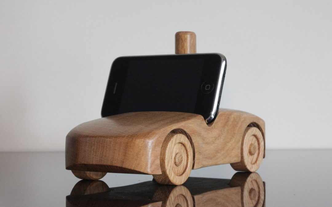 A oak wood car holding a phone