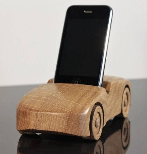 Oak wood phone stand in the shape of a car - front and side visible, black phone stood tall