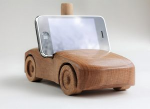 Oak wood phone stand in the shape of a car f- front and side visible, black phone
