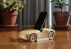 Oak wood phone stand in the shape of a car - mostly side visible on a shiny oak table